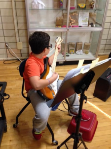 Third grader Ivan Hyde performs on his guitar at Hillis Poetry Night!